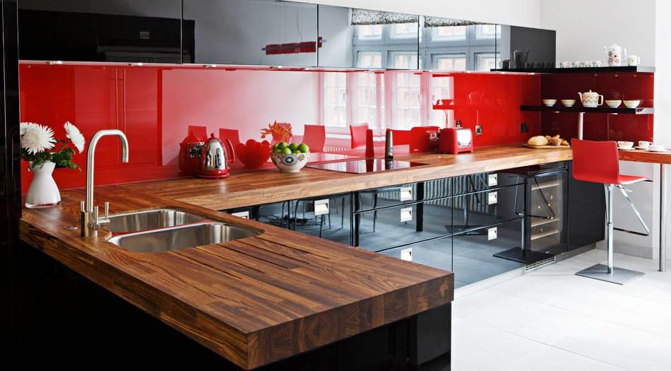 Ярко-красный фартук и деревянная столешница на чёрно-белой кухне