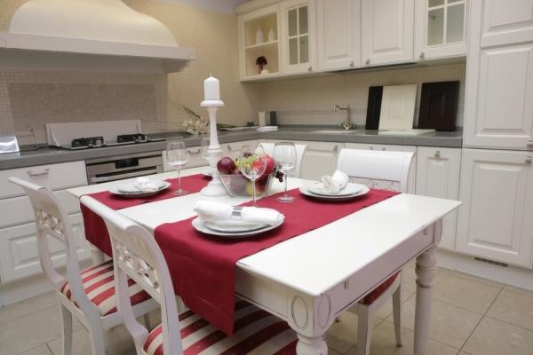 Красные элементы в декоре кухни: скатерти и обивка стульев