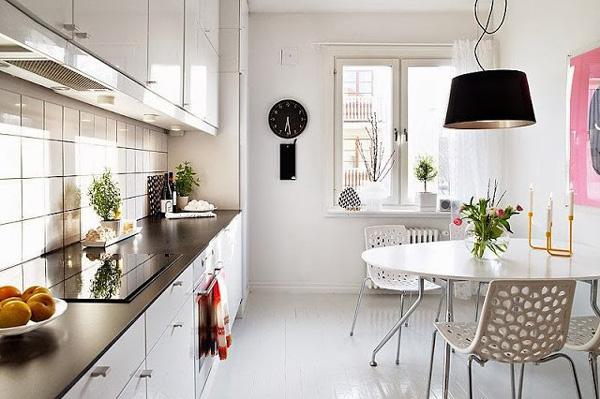 Черные часы на белой стене кухни