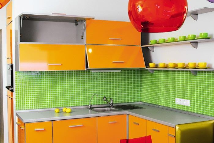 Оранжевая мебель и зелёный фартук на кухне