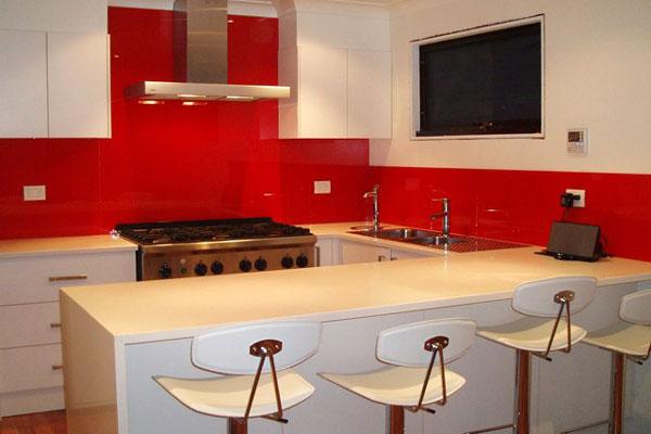Практичный красный фартук на фоне белой мебели