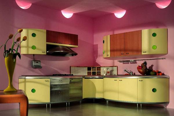 Желтая угловая кухня на фоне розовых стен
