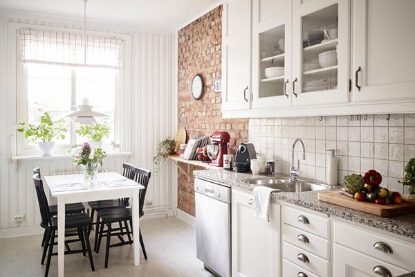 Белая уютная кухня залита светом от окна